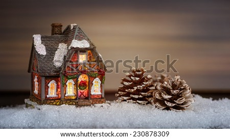 Christmas house and pine cone in the snow - stock photo