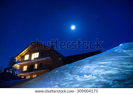 Christmas house in winter mountains at night. Snow landscape with blue dark sky with milkyway and many stars. Ukraine, Carpathians, Europe - stock photo