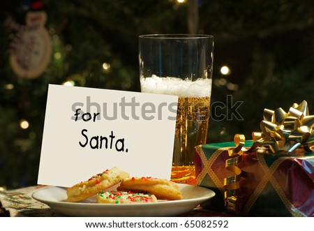 Christmas, humorous image of a note left for Santa from the children on Christmas eve  with cookies on a plate and a tall glass of cold beer with sparking Christmas lights and decorations. - stock photo