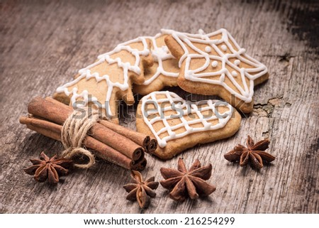 Christmas iced gingerbread cookies with various spices on wood background. - stock photo