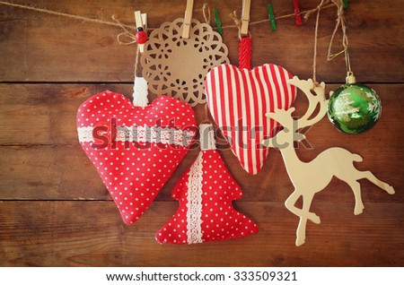 Christmas image of fabric red hearts and tree. wooden reindeer and garland lights, hanging on rope in front of wooden background