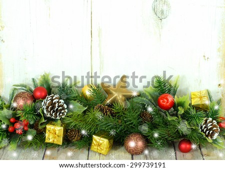 Christmas image of pine boughs and holly with scattered red and gold presents and decorations in front of a white washed rustic background. Digital sparkles and snowflakes have been added.  Copy space