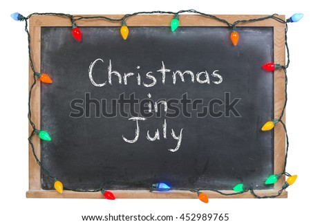 Christmas in July written in white chalk on a black chalkboard surrounded with colorful lights isolated on white