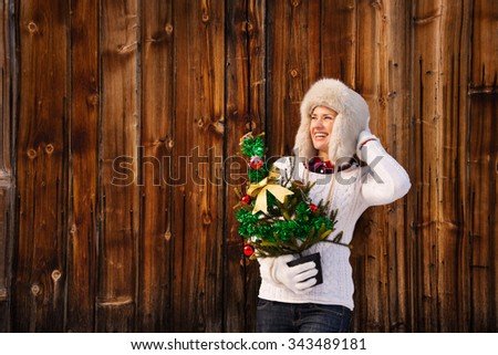 Christmas in the country style. Happy young woman in white knitted sweater and furry hat holding Christmas tree in the front of rustic wood wall and looking on copy space - stock photo