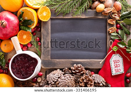 Christmas ingredients background with chalkboard, oranges, cranberry, nuts and spices - stock photo