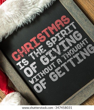 Christmas Is the Spirit of Giving Without a Thought of Getting written on blackboard with santa hat - stock photo