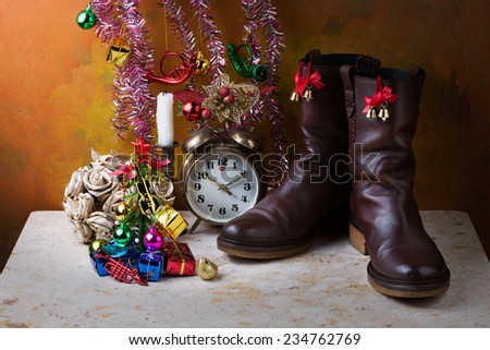 Christmas items with brown genuine haft boots on grunge with dry flowers and candles still life art photography - stock photo