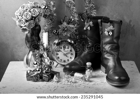 Christmas items with brown genuine haft boots on grunge with dry flowers and candles still life art photography black and white version - stock photo