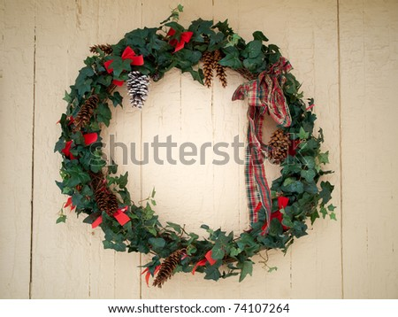 Christmas ivy wreath on painted old wall in winter