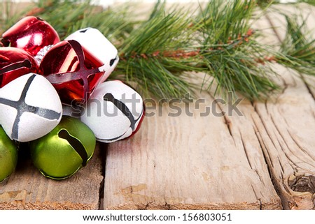 Christmas Jingle bells and a pine branch on a rustic wooden plank - stock photo