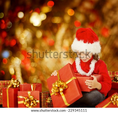 Christmas Kid Opening Present Gift Box, Happy Child in Santa Hat, Smiling Girls In Red Cap Funny Looking Toys - stock photo