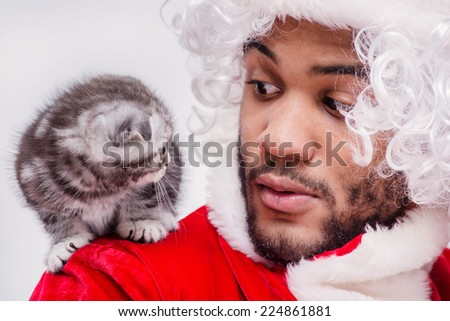Christmas kitten from Santa Claus in the New Year. African Santa Claus holding a kitten on her shoulder and looking at each other while sitting on an i white background on Christmas Eve at New year - stock photo