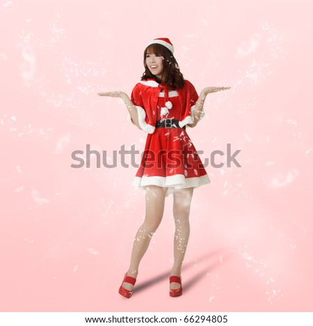 Christmas lady standing with flakes showing surprised expression over pink background. - stock photo