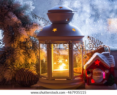 Christmas lantern and decorations on frozen window