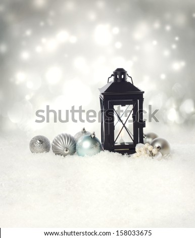 Christmas lantern and ornaments on the snow in a silver shinning night - stock photo