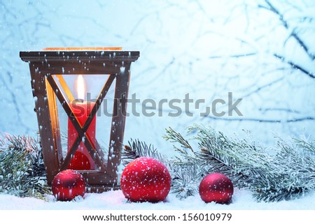 Christmas lantern and red balls with snowfall,Closeup. - stock photo