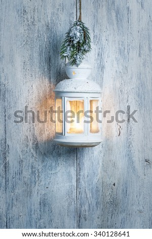 Christmas lantern and snow on wooden background - stock photo