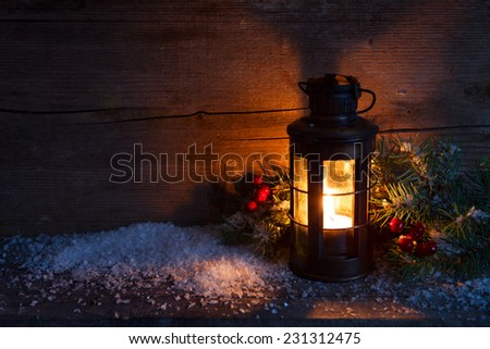 Christmas lantern, fir twigs and artificial snow in night on old wooden background. - stock photo