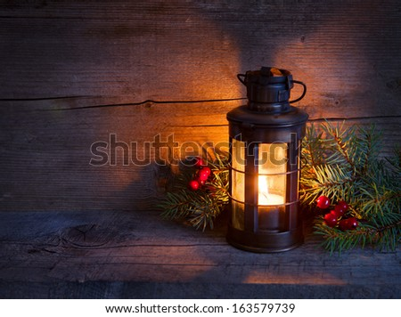 Christmas lantern  in night on old wooden background. focus on the wick candles - stock photo