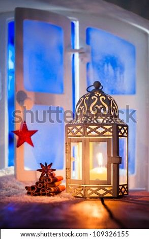 Christmas lantern with a glowing candle burning in a window illuminating dried seasonal spices with copyspace - stock photo