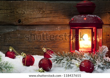 Christmas lantern with baubles fir and snow on vintage wooden background in night - stock photo