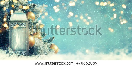 Christmas lantern with Christmas decoration on the snow