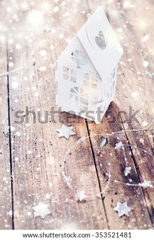 Christmas lantern with snowfall and decorative ornaments  on wooden board - stock photo