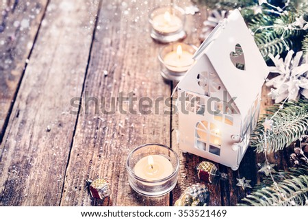 Christmas lantern with snowfall and decorative ornaments  on wooden board. Christmas background with copyspace - stock photo