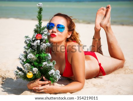 Christmas lifestyle portrait of stunning woman lying on the beach. Smiling girl holding in her hands a Christmas tree. Christmas girl wearing stylish red bikini and sunglasses. Tanned slim body  - stock photo