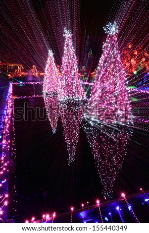 Christmas Light Streaks. Christmas lights and a fountain reflect in a pond. Streaks of light from a camera zoom and slow shutter.  - stock photo
