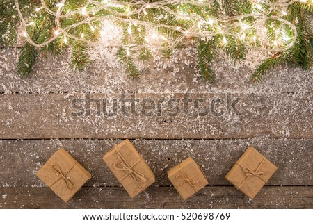 christmas lights and decorations with snow on the wooden background