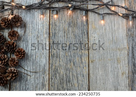 Christmas Lights and Pine cones on Rustic Wood Background - stock photo