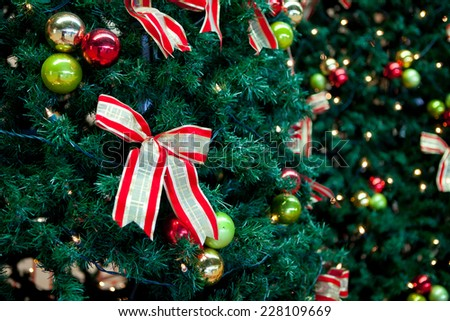christmas lights and ribbons hanging in a tree  - stock photo