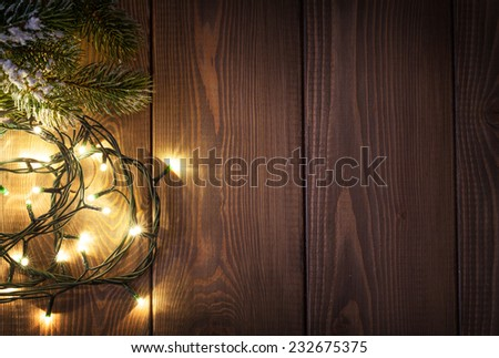 Christmas lights and snow fir tree over wooden background with copy space - stock photo