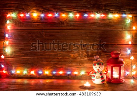 Christmas lights and vintage lantern and snowman on wooden background. Frame of lights. Merry Christmas.