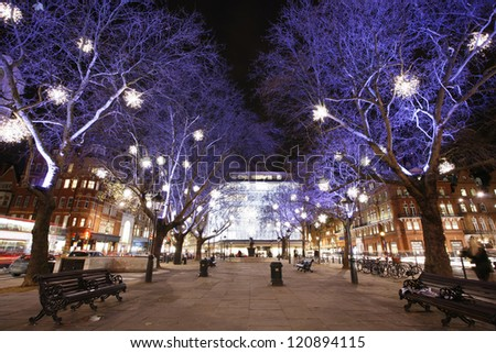 Christmas Lights Display on Sloane Square in Chelsea, London. The modern colorful Christmas lights attract and encourage people to the street. - stock photo