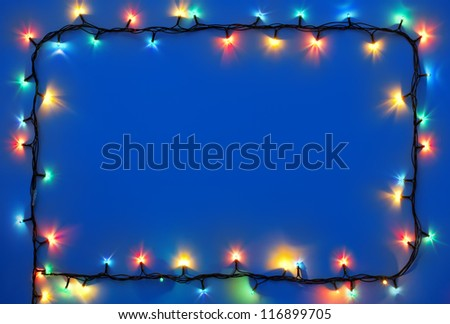 Christmas lights frame on dark blue background with copy space.Decorative garland - stock photo