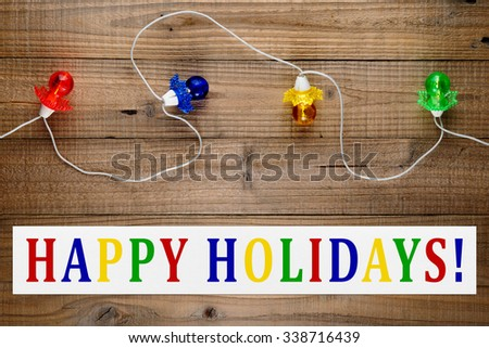 Christmas lights garland and happy holidays text on wooden background - stock photo