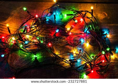 Christmas lights on wood background - stock photo