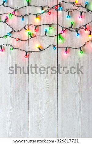 christmas lights over white painted planks for background - stock photo