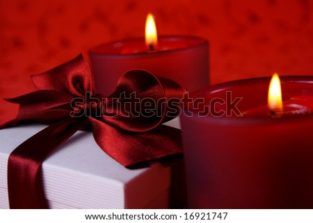 christmas lights - two candles and christmas gift box on red background - stock photo