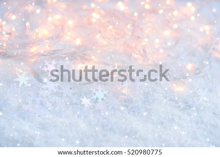 Christmas lights with snowflakes on snow. Christmas festive background