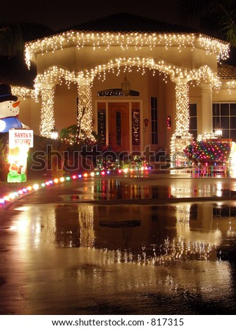 Christmas lit entryway reflected in wet concrete driveway - stock photo