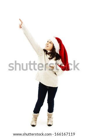Christmas little girl pointing at copy space standing in full length. Isolated on white background - stock photo