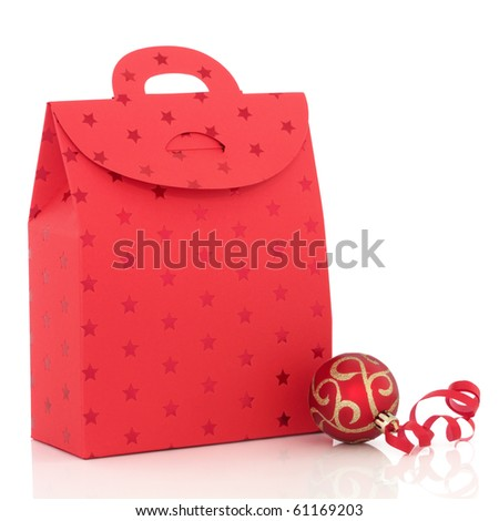 Christmas luxury gift bag and red and gold sparkling bauble with ribbon, isolated over white background.