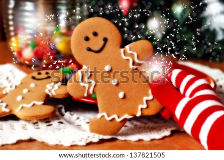 Christmas Magic.  Holiday still life of colorful gloved hand holding a smiling gingerbread man with gumdrops and christmas tree in background. Enhanced for enchanted effect. - stock photo