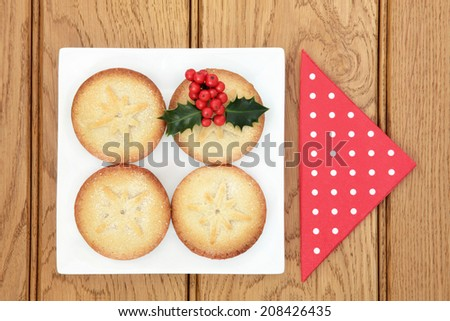 Christmas mince pie cakes on a plate with holly and red serviette over oak background. - stock photo