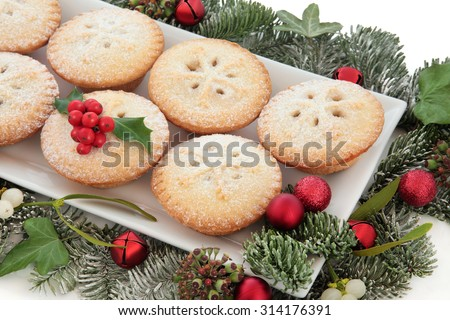 Christmas mince pie cakes on a plate with red baubles, holly, mistletoe and winter greenery over white background. - stock photo