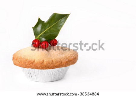 Christmas mince pie topped with holly leaves and red berries, over white background. - stock photo
