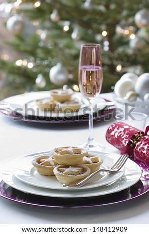 Christmas mince pies; cracker and champagne flute on dining table - stock photo